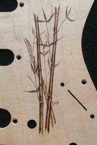 Close-up view of bamboo design woodburned on maple veneered aluminum pick guard - raw wood