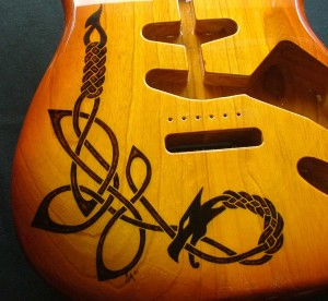 Close-up view of Celtic dragon design woodburned on guitar body