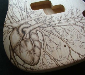 SOLD - Close-up view of human heart design woodburned on P bass guitar body - raw wood