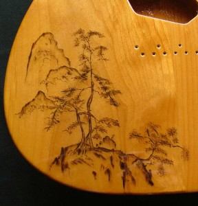 Close-up view of traditional Japanese landscape design woodburned on guitar body