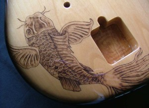 Close-up view of Koi fish design woodburned on guitar body
