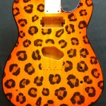 Leopard print pattern woodburned on guitar body with orange burst