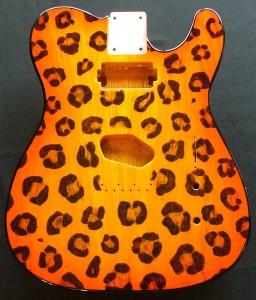 Leopard print pattern woodburned on guitar body with orange burst