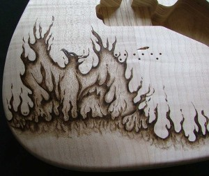 SOLD - Close-up view of Phoenix design woodburned on guitar body - raw wood