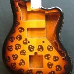 Skulls pattern woodburned on guitar body with dark burst finish