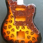 Skulls pattern woodburned on guitar body with optional pick guard