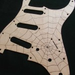 Spider web design woodburned on maple veneered aluminum pick guard - raw wood