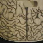 Close-up of human brain design woodburned on bass guitar body - raw wood.