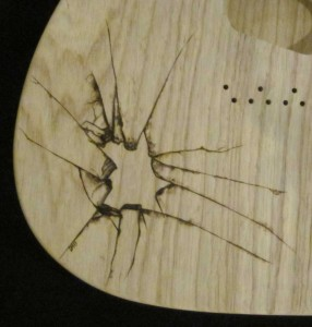 Close-up view of shattered glass design woodburned on guitar body - raw wood.