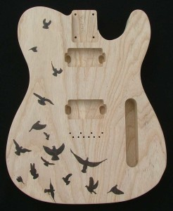 Design of birds woodburned on Ash Telecaster guitar body - raw wood