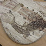Close-up view of koi fish woodburned on spalted maple guitar body - commissioned piece