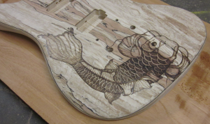 SOLD - Close-up view of koi fish woodburned on spalted maple guitar body - commissioned piece